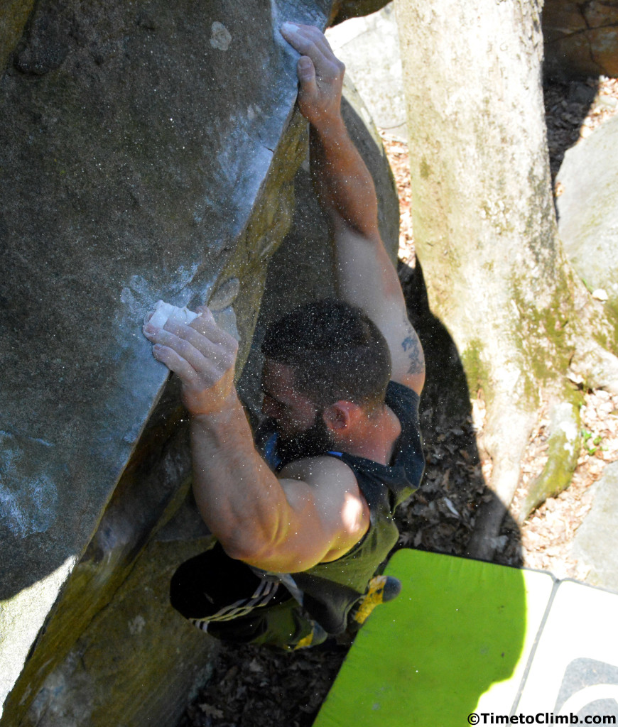 Mike Kleban bouldering in Half Moon with chalk dust in the air