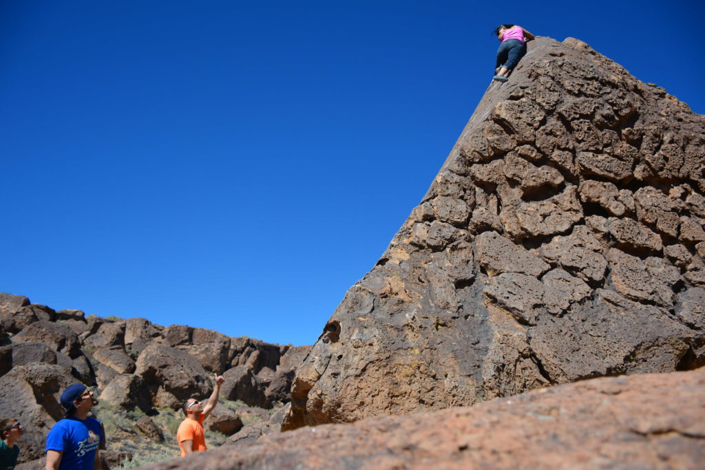 Ann Marie at the top of Celestrial Trail V0 in the Happy Boulders in Bishop California - MDV