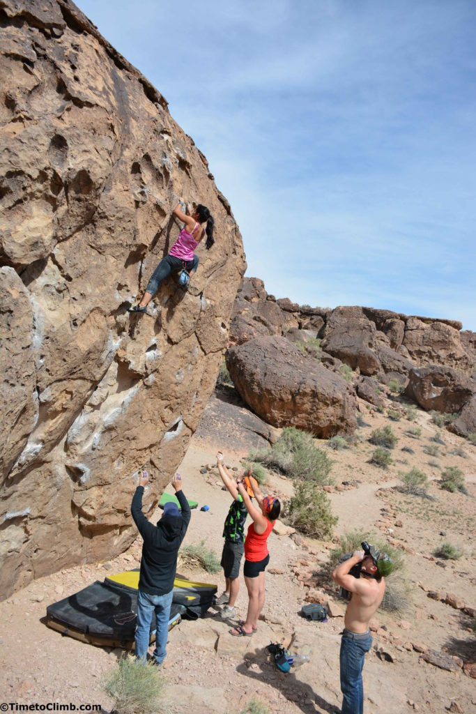 Ann marie climbing in Bishop on the Serengeti Boulder while being spotted