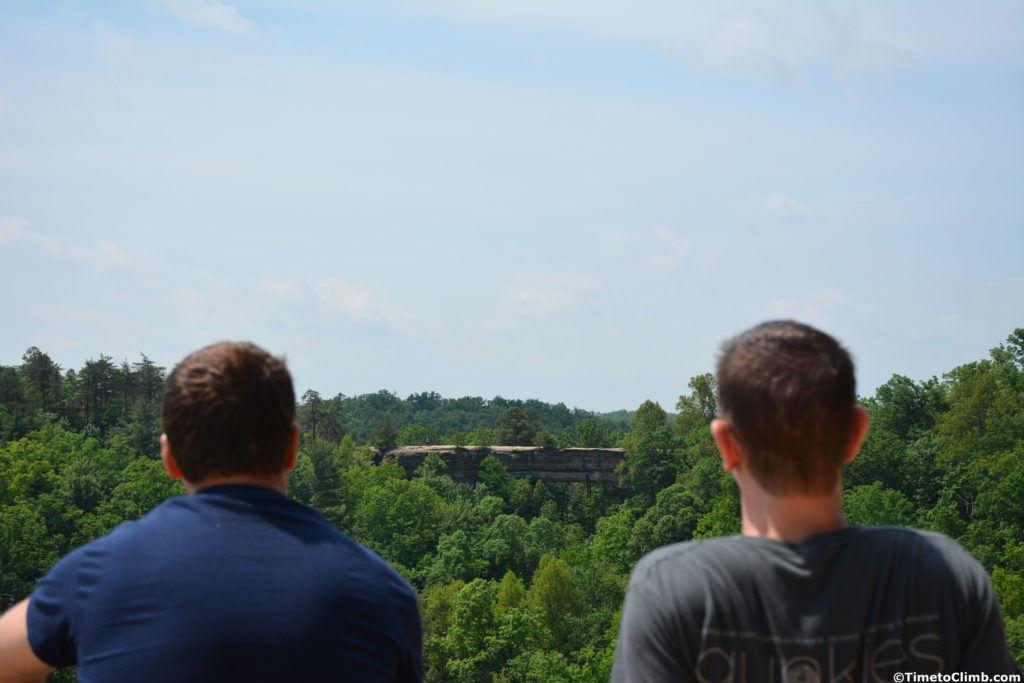 Matt and Kevin sitting looking at Natural Bridge from the adjact cliff