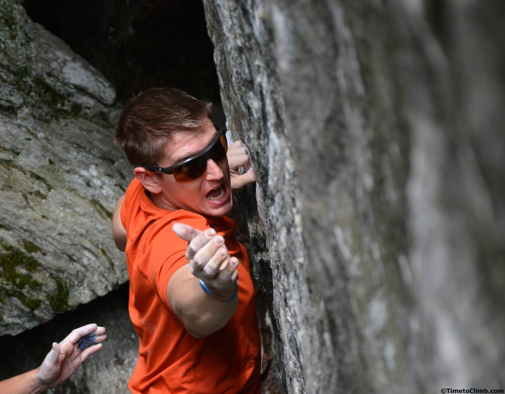 Andrew Messick giving a shout while going for it on Dojo V6 bouldering in Smuggler's Notch, Vermont
