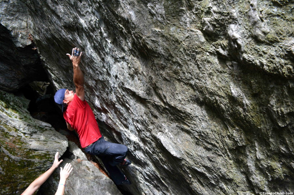 Melvin Rivera reaching up for the crimp hold on Triscuit V7 bouldering in Smuggler's Notch Vermont