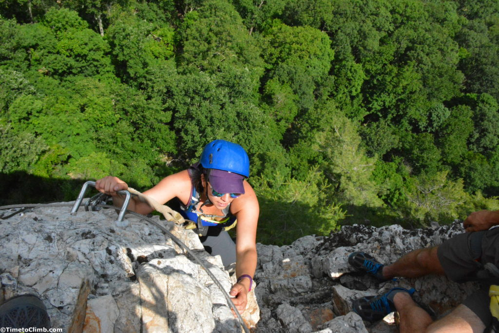 Michele reaching the top of the head wall on the via feratta in Nelson Rocks