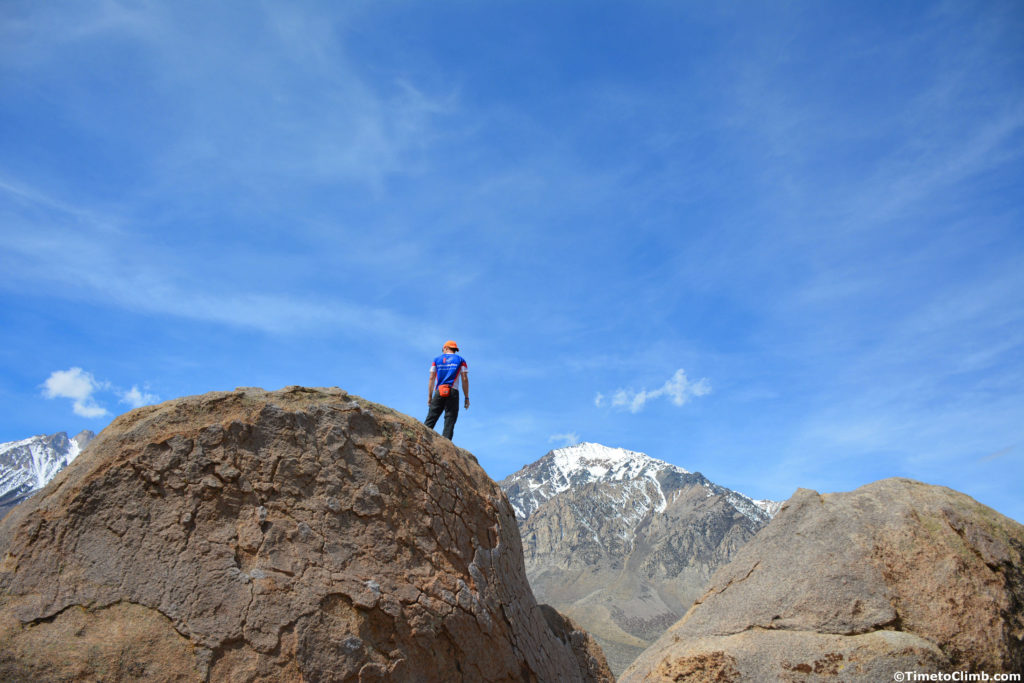Andrew Messick standing at the top of the Birthday Boulders climbing in Bishop