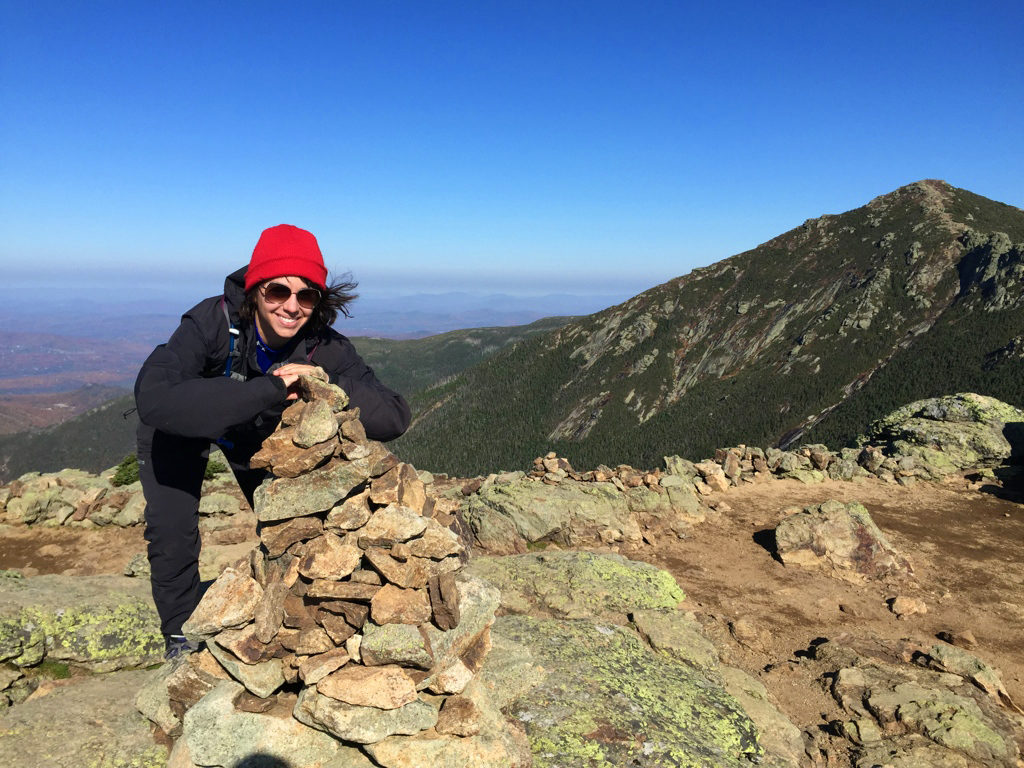 Michele hovering over a cairn, with Mount Lincoln in the background.